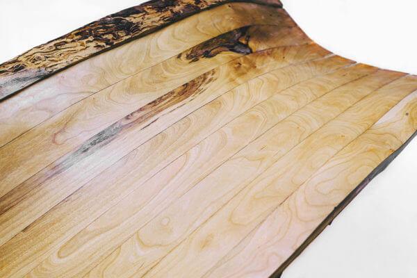 Wood grain and bark edges provide process narrative and clarify zero waste concept.